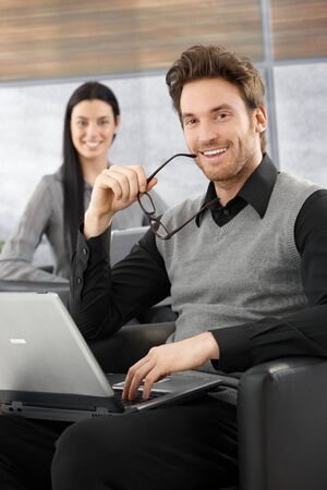 Handsome young businessman sitting in office lobby, working on laptop, smiling at camera happily. photo