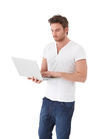young unshaven: Casual young man standing over white background using laptop.