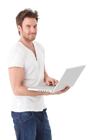 man standing alone: Young man browsing internet on laptop, standing over white background, smiling.