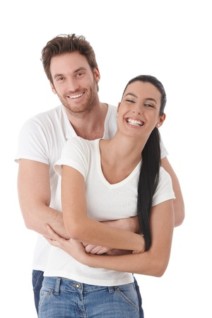 Happy couple standing over white background, laughing. photo