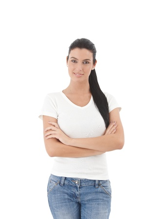 Portrait of cheerful young woman standing arms crossed over white background, smiling. photo