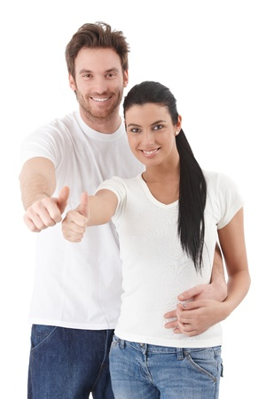 Happy young couple standing over white background, showing thumb up, smiling. photo