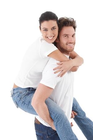 amigos abrazandose: Feliz pareja amorosa sonriendo, abraz�ndose unos a otros, hombre pickaback libros de mujer. Foto de archivo