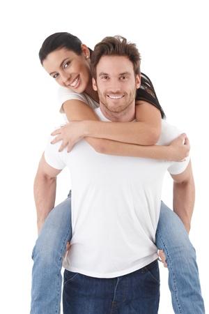 amigos abrazandose: Atractiva pareja joven enamorado, hombre llevando pickaback mujer, sonriendo felizmente. Foto de archivo