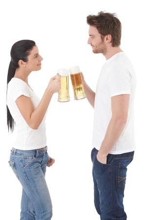 ni�o parado: Joven pareja beber cerveza, chocan, sonriendo.