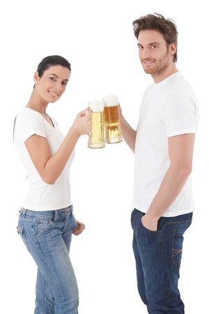 Attractive young loving couple clinking glasses, drinking beer, smiling over white. photo
