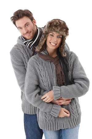 Young loving couple wearing the same sweater, smiling. photo