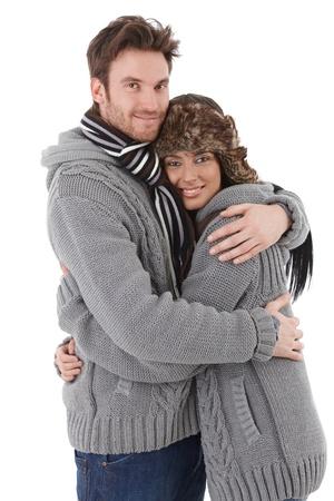 amigos abrazandose: J�venes amantes de la pareja abraz�ndolo entre s�, usando el mismo su�ter, sonriendo.