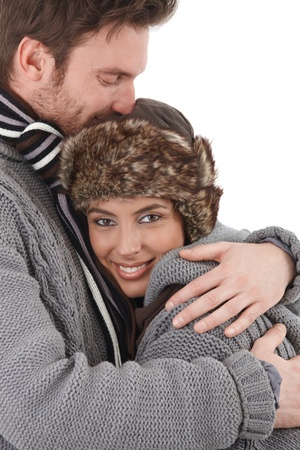 looking at each other: Happy young couple cuddling each other with love, dressed up warm, smiling. Stock Photo
