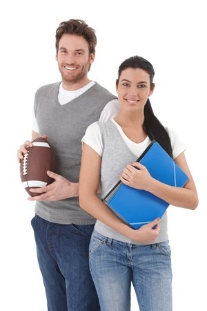waistcoat: Cheerful university students holding folders and rugby ball, smiling. Stock Photo