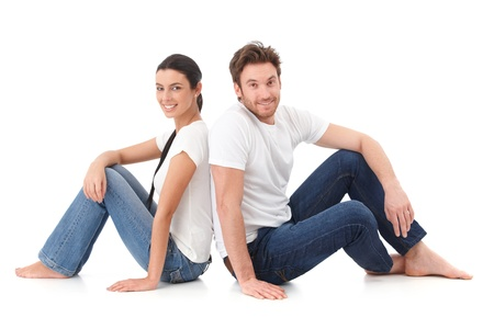 Happy couple sitting on floor with back to each other, smiling. Stock Photo - 9201713
