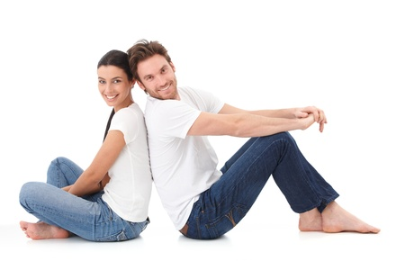Cheerful young couple sitting with back to each other on floor, smiling happily. photo