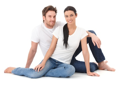 Attractive young loving couple sitting on floor, smiling happily. photo