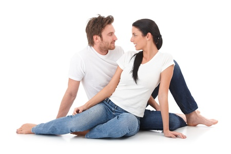 Romantic young couple sitting on floor, giving each other the eye, smiling photo