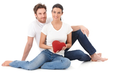 looking at each other: Loving couple sitting on floor, holding red heart in hand, smiling.