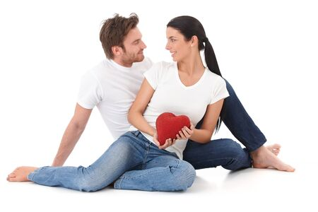 Romantic couple making eyes at each other, holding red pillow heart, smiling. photo