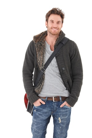 Casual young man in jeans and cardigan smiling over white background.