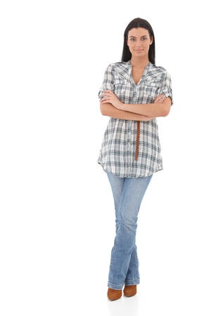mani incrociate: Bella giovane donna in piedi su sfondo bianco, sorridendo a braccia incrociate.
