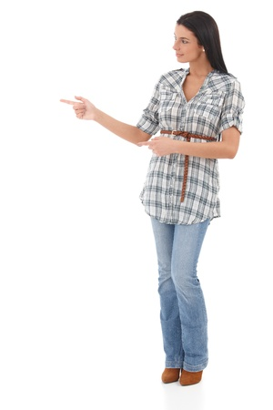 Attractive young woman standing over white background, pointing and looking to the right, smiling. photo