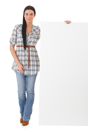 Attractive young woman standing over white background holding a blank sheet. photo