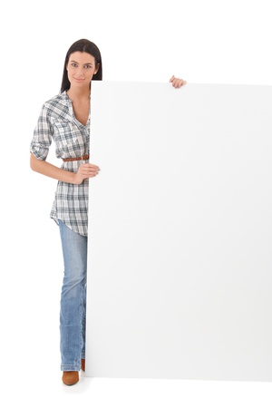 Pretty girl standing with a huge blank sheet. photo