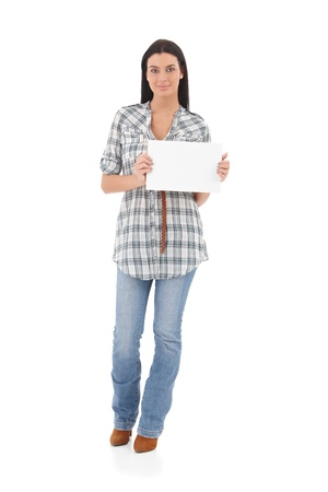 Casual young girl holding a blank sheet in hands, smiling. photo