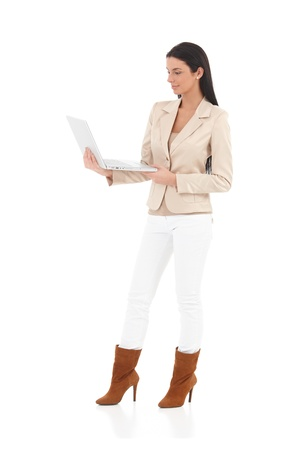 Trendy woman standing with laptop in hand, smiling. photo