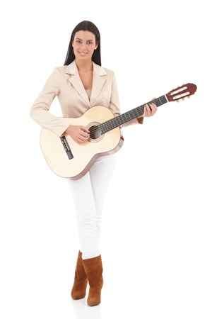 Pretty young girl playing guitar, smiling. photo