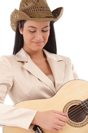 Attractive female guitar player lost in music, smiling eyes closed. photo
