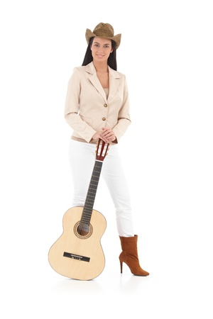 Happy female guitar player standing with her guitar, smiling. photo