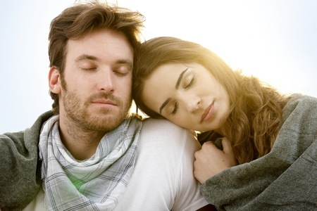 fantasize: Romantic young couple sitting and resting with closed eyes in summer sunshine. Stock Photo
