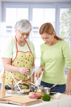 Senior mother and daughter cooking together in kitchen. photo