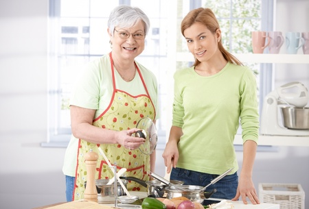 stirring: Pretty girl cooking with senior mother, smiling, stirring food.