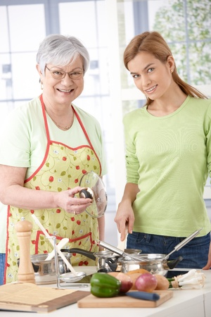 mature old generation: Senior mother and attractive daughter cooking together in kitchen, smiling.