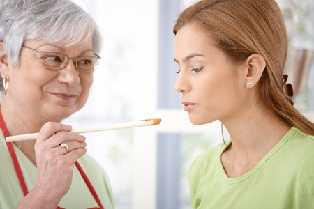 Mother and daughter cooking together, mother offering sauce to taste. Stock Photo - 9209255
