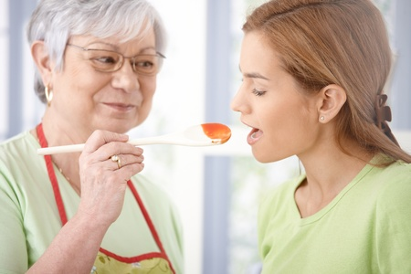 Pretty young girl tasting sauce from wooden spoon prepared by her senior mother. Stock Photo - 9209257