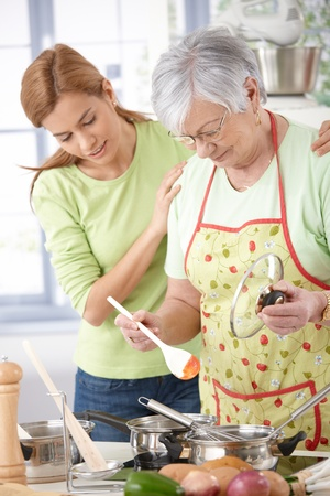 Senior mother preparing food in kitchen, daughter hugging from behind and looking curiously. Stock Photo - 9209256