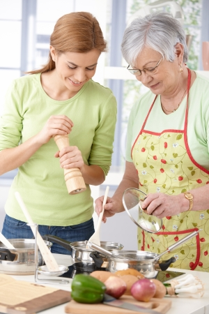 Senior mother and young daughter preparing food in kitchen, having fun, smiling. Stock Photo - 9209319
