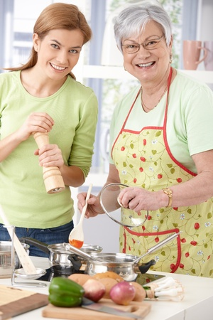 kitchen apron: Happy mother and pretty daughter preparing food together in kitchen, smiling, looking at camera. Stock Photo
