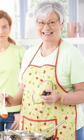 Senior woman cooking in kitchen, smiling happily, daughter standing at background. photo