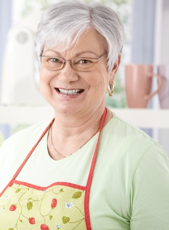 Portrait of senior woman smiling happily, wearing cooking apron. photo