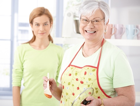 Cheerful senior mother cooking in kitchen, daughter watching from background. photo
