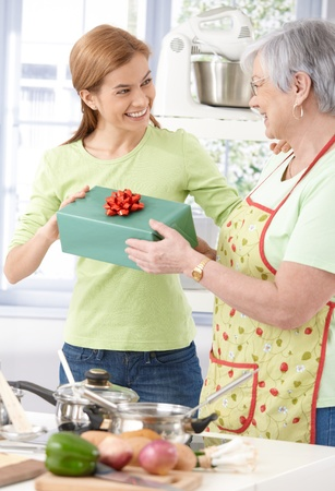 receive: Attractive young woman giving present to her mother, standing in kitchen, both smiling.