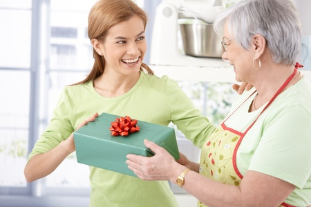 both: Happy young female presenting her mother with wrapped gift, both smiling.