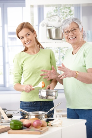 Senior mother and daughter cooking together, smiling, looking at camera. photo