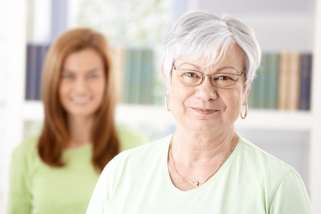 Portrait of mature woman smiling, daughter standing at background. Stock Photo - 9208738