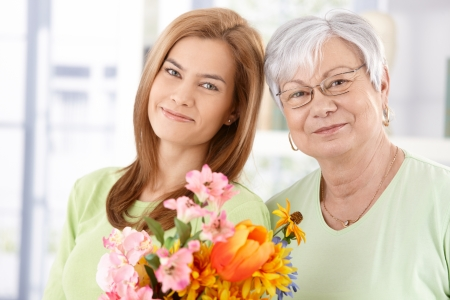 Portrait of senior mother and daughter at Mothers day, having flowers, smiling.