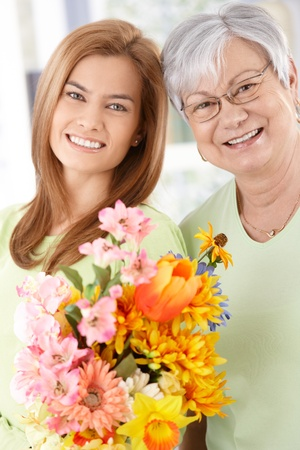 blonde mom: Senior mother and daughter smiling happily at Mothers day, having flowers. Stock Photo