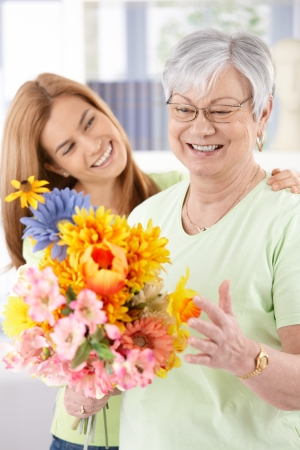 Elderly woman and daughter smiling happily at mothers day, having flowers.