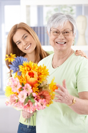 getting together: Happy senior mother and daughter smiling at mothers day, holding flowers. Stock Photo